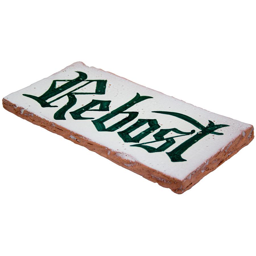 Vista 3/4 del rètol de ceràmica rústic amb 'Rebost'