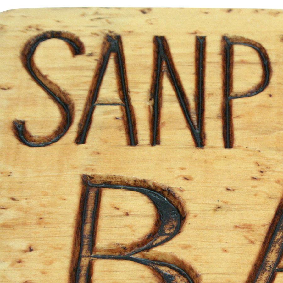 Detall de les lletres tallades a la fusta