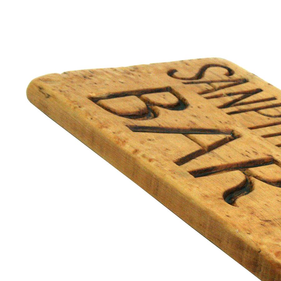 Vista 3/4 del rètol de fusta amb lletres tallades